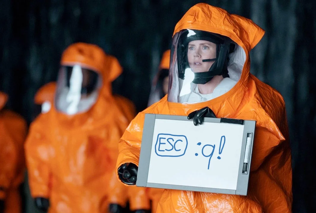 "Woman in environmental suit holding sign: ""ESC :q!"""